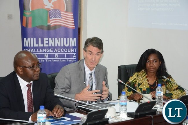 Resident Country Director Millennium Challenge Corporation Steve Marma speaking whilst flanked by CEO Millennium Challenge Account Pamela Bwalya and Director Operations Millennium Challenge Account Israel Banda during Millennium Challenge Water meeting at Parliament building