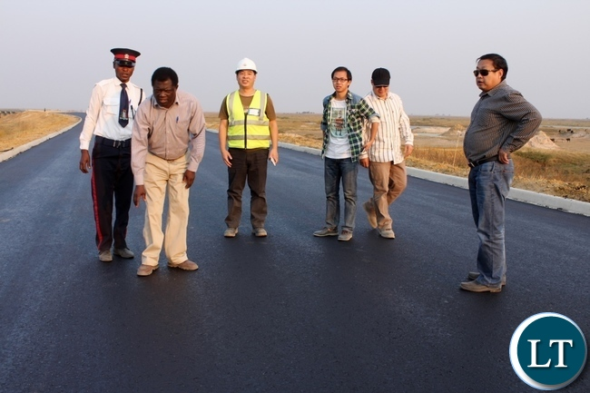 Mongu District Commissioner Susiku Kamona (l) looking closely on the new tarmac  road as AVIC International Zambia Limited Site Manager Chen Yiju (r) looks on during a tour to inspect work progress on the Mongu-Kalabo Road Project