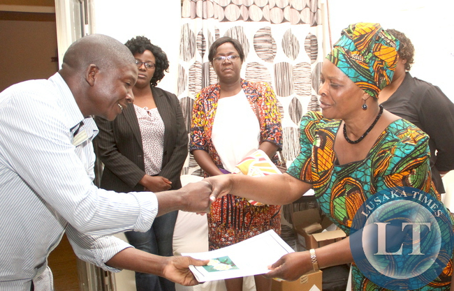 First Lady Esther Lungu presents a certificate to Induna David Sitali after he participated in a Cervical Cancer training workshop at Dolphin Lodge in Mongu, Western Province of Zambia on Saturday, August 15,2015 -Picture by THOMAS NSAMA