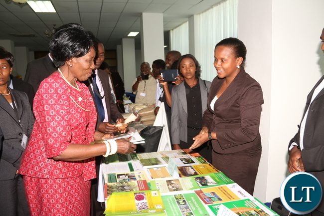 Ugandan PELUM Country RepresentativeCoordinator distributes an Agriculture booklet to Veep and Acting President Dr Inonge Wina