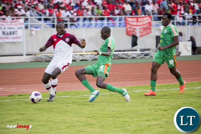 Zesco United midfielder Misheck Chaila (c) battles for the ball with a Nkana striker Fred Tshimenga.