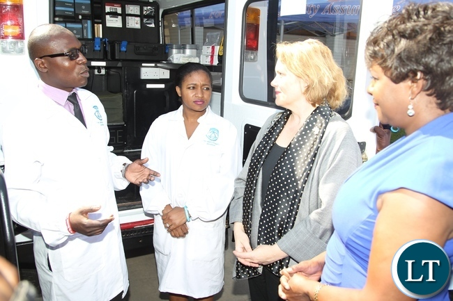 Zambia Bureau of Standards Lab-Analyst Dominic Phiri flanked by Zambia Bureau of Standards Lab-Technician Sithle Nkonde explaining on the equipments Minister of Commerce and Trade Margaret Mwanakatwe (r) and UNDP Country Co-odinator Janet Rogan (2nr) shortly hand over ceremony