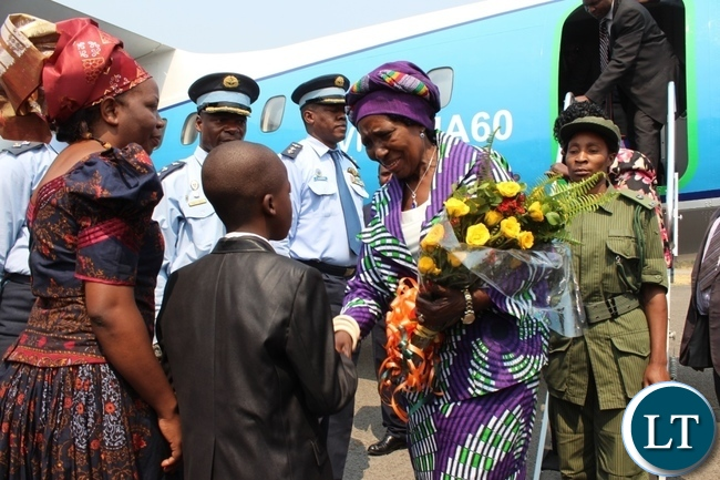 Vice President Inonge Wina (r) receives a bouquet from Joe Makungwe jr. (c) on arrival at Mongu Airport yesterday on a five days tour inspecting some developmental projects and interacts with the people of Western Province.