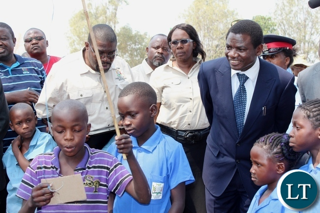 Education Deputy Minister David Mabumba (r) and Western Province Education Officer Loveness Mubisi (c) observing a pupil reading during the celebration of International Literacy Day at Mulambwa Primary School in Mongu