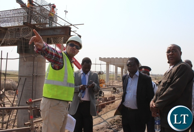 Rankin Consultant Company Resident Engineer Salah Gad (l) explaining the work progress of Mongu-Kalabo Road Project to Zambezi Region Council Leadership of Namibia, Governor Col. Lawrence Sampofu (r) and Mongu District Commissioner Susiku Kamona (c) during the tour of the project