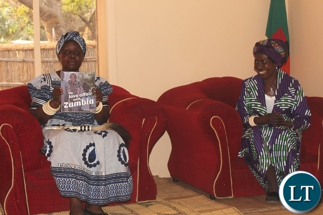 Her Royal Highness Litunga La Mboela (l) of Lwambi Chiefdom displays a book ''My Love Affair with Zambia'', from Dignity Zambia CEO Sandy Clark as Vice President Inonge Wina (r) looks on during the courtesy call at Muoyo Palace in Nalolo District