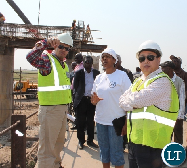 Rankin Consultant Company Resident Engineer Salah Gad (l) explaining the work progress of Mongu-Kalabo Road Project to Namibian High Commission First Secretary Hellen Ndandi (c) as AVIC International Zambia Limited Site Manager Chen Yiju (r) looks on during the tour of the project
