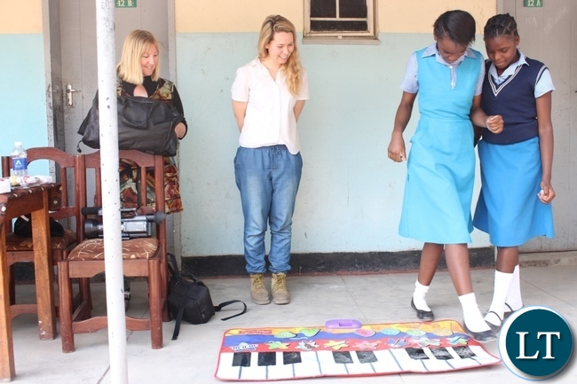 Holy Cross Girls Secondary School pupils trying how to play the floor piano as Dignity Zambia CEO Sandy Clark (l) and Australian Music Teacher Cate Dyer (c) observe during the donation of assorted items to the school in Mongu