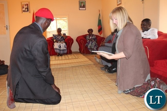 Dignity Zambia CEO Sandy Clark (r) receives the Lwambi chiefdom Development Strategic Plan for 2015-2019 guidelines from Her Royal Highness Litunga La Mboela through Induna Biundan'ono (l) during the courtesy call at Muoyo Palace in Nalolo District