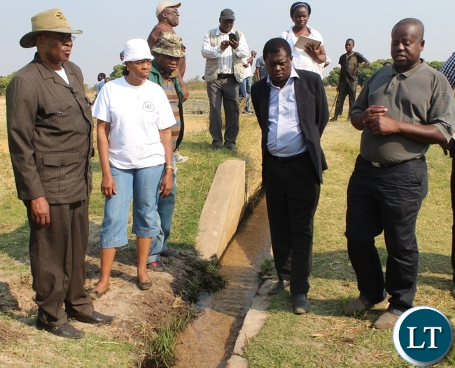 Sefula Irrigation Scheme Camp Extension Officer Angelo Silumesii (r) explains the importance of the canal in a sandy terrene to Zambezi Region Council Leadership of Namibia, Governor Col. Lawrence Sampofu (l), Namibian High Commission First Secretary Hellen Ndandi (2nd l) and Mongu District Commissioner Susiku Kamona (2nd r) during the tour of the agriculture projects in Mongu