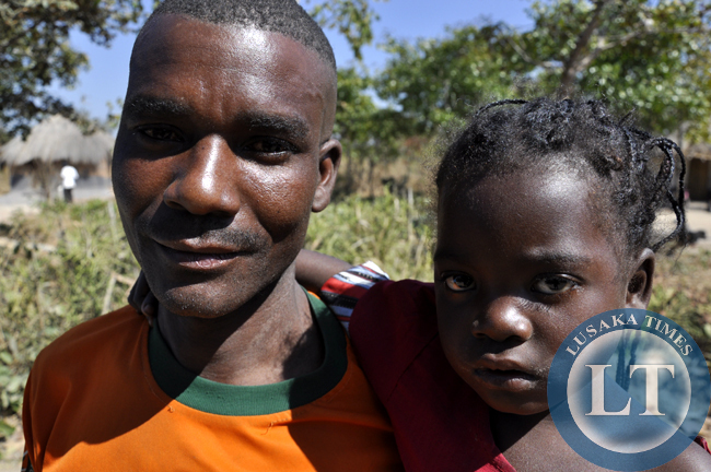 An unideitfied father with his daughter at captured in chief Mulala's area in Luwingu. There are many cases of child marriages and school dro-outs in the area