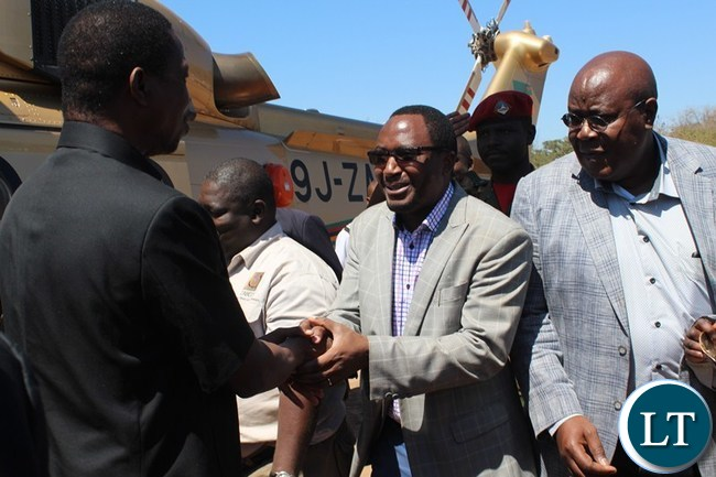 PRESIDENT Edgar Lungu shakes hands with Sinazongwe Member of Parliament Richwell Siamunene who is also Defence Minister, while Southern Province Permanent Secretary Sibanze Simuchoba (r) looks on at Sinazeze School grounds in Sinazongwe district on Wednesday. The President was in Sinazongwe to launch the ground breaking ceremony for Bottom road lot two (2).