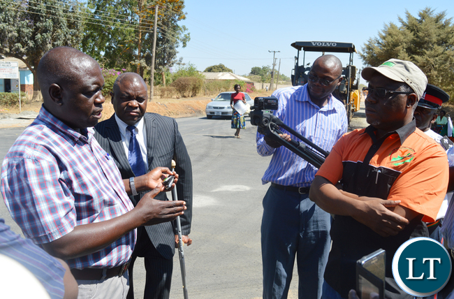 Gladstone resident engineer Christopher Situmbeko (left) explains to Southern Province Minister Nathaniel Mubukwanu (in a cap) progress on upgrading of 30 kilometres urban township roads in Choma by Jiangsu International Economic Technical Corporation. Picture by CHILA NAMAIKO