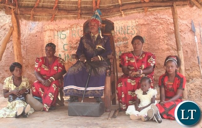 Chief Matebo with his wives, Cydah (l) and Phillies (r ) follow the proceedings of the Kuvuluka Kishakulu tradition ceremony at the royal grounds in Solwezi