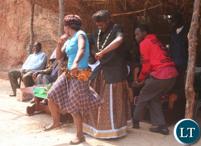 Acting Solwezi mayor Brian Kajoba (r ) joins Nsomo cultural group dancer Felistus Malingosa in dancing beauty is made and fined song during the Kuvuluka Kishakulu tradition ceremony at chief Matebo's grounds in Solwezi on Saturday as Acting Solwezi district commissioner Muyobo Shimabale (far left) looks on