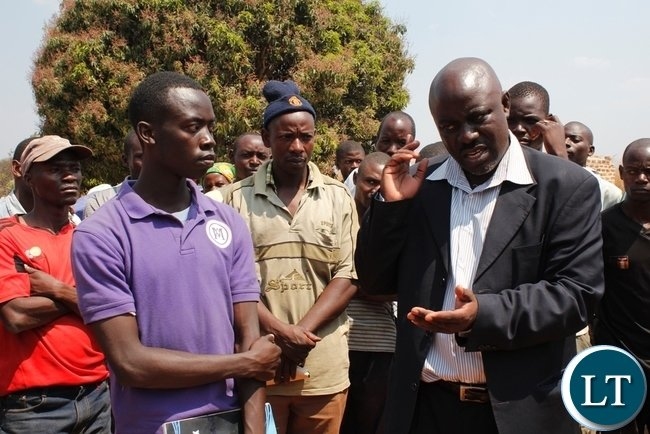 ut-going Acting Mbala District Commissioner, Felix Mungaila talking to FRA depot clerk, Rhema Siwelwa at Mambwe Mission Satellite depot