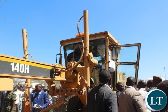 President Edgar Lungu (in white dust coat) embarking on a grader to lunch the ground breaking for Bottom road of lot two (2 ) in Sinazeze area in Siavonga district