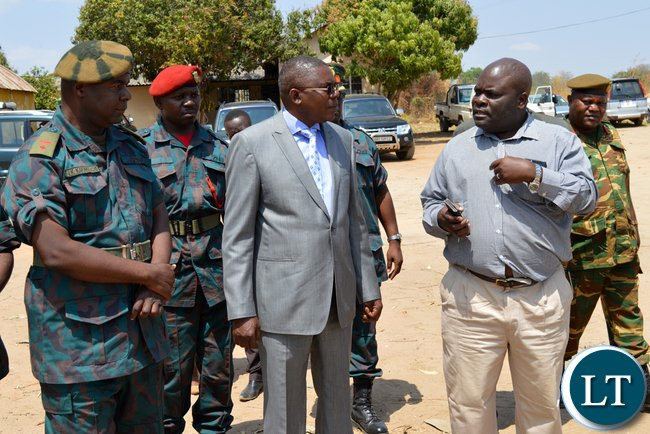 Southern Province Rural Roads Unit provincial engineer Edward Ntinda (right) talks to Defence deputy Minister Christopher Mulenga (in a suit) while Zambia National Service unit Choma commanding officer Lieutenant-Colonel Jimmy Kafumukache (far left) listens during tour of RRU offices in Choma