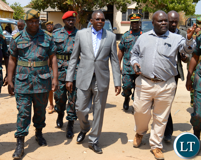 Southern Province Rural Roads Unit provincial engineer Edward Ntinda (right) takes Defence deputy Minister Christopher Mulenga (in a suit) and Zambia National Service unit Choma commanding officer Lieutenant-Colonel Jimmy Kafumukache (far left) on tour RRU offices in Choma