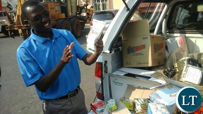 Competition and Consumer Protection Commission (CCPC) Southern Province investigator Chipapa Matyola displaying the expired and defective products in Livingstone