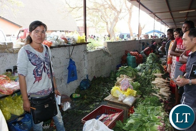 A Chinese Woman Selling Vegetables in a Lusaka Market