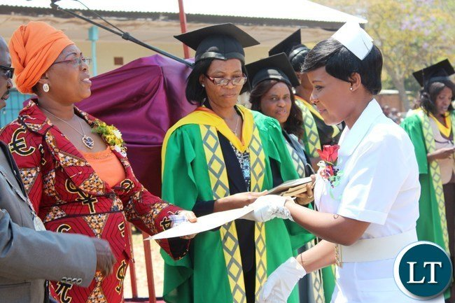AGNESS Mwale from St. Francis school of nursing receives a certificate from Eastern Province Assistant Secretary, Beenzu Chukuba, during the graduation ceremony of nurses and midwive from Mwami Adventis, Chipata General and St. Francis schools of nursing held in Chipata