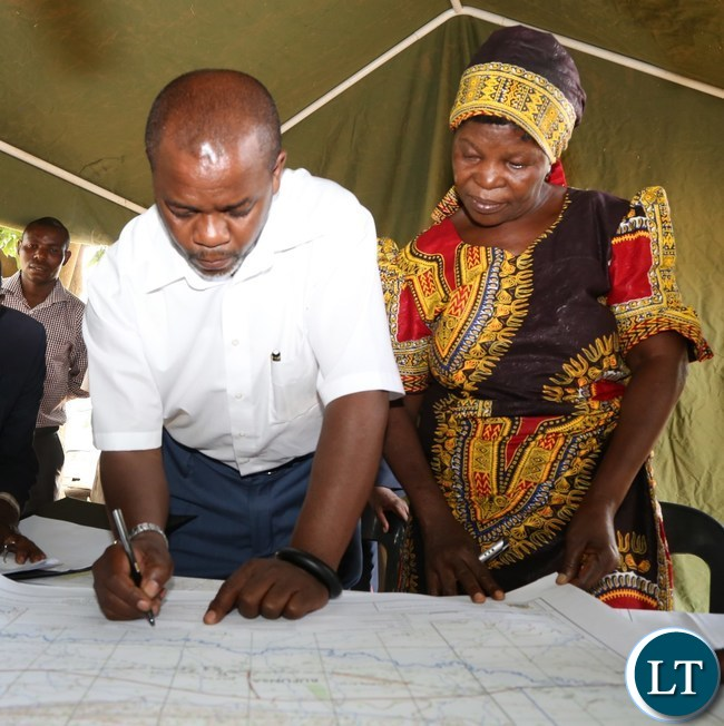 Lusaka Province Permanent Secretary Stardy Mwale signs the plan while Her royal highness chieftaniss Mpanshya looks on during the official hand over of 2000 hectare's of land for the construction of government infrastructure in rufunsa district