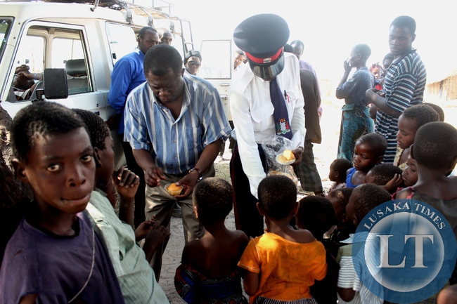 Mongu District Commissioner Susiku Kamona (l) gives food to children of victims of Imuba Village of Katongo Lower area in Mongu whose entire village was burnt to ashes on Sunday, October 18, 2015.