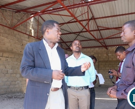 Mongu District Commissioner Susiku Kamona (l) confers with Tusano Mango Processor CEO Mwisiya Waluka (r) during the inspection of work progress on projects funded by Citizens Economic Empowerment Commission (CEEC) in Mongu