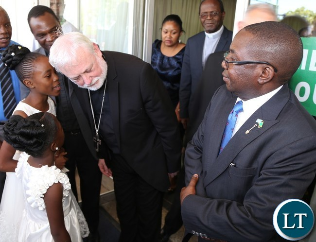 -His excellency Mgrs.Poul Richard Gallgher (L) flanked by Foreign Affairs Deputy Minister Reyford Mbulu (r) being welcomed by Chipego Banda 9 years old and Lubuto Chitupila at Kenneth Kaunda International Airport yesterday 07-11-2015. Picture by ROYD SIBAJENE/ZANIS