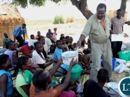 DMMU District Secretary Matakala Mbangweta (r) distributing kitchen utensils to disaster victims of a firestorm which burnt the entire Imuba Village to ashes in Lower Katongo area in Mongu.