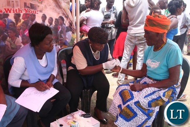 A nurse from Solwezi general hospital Cynthia Muyoya (m) checks sugar levels of a 70 year old Esnart Mashilipa (r ) of Kazomba compound during random sugar level checking to commemorate this year's World Health Diabetes Day held at Kyawama school grounds last Saturday in Solwezi as her counterpart Bupe Sachibobe (l) looks on.