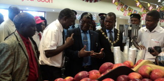 Copperbelt Province Permanent Secretary Haward Sikwela being shown the products by Shoprite Director Charles Bota at Chingola Shoping Mall.
