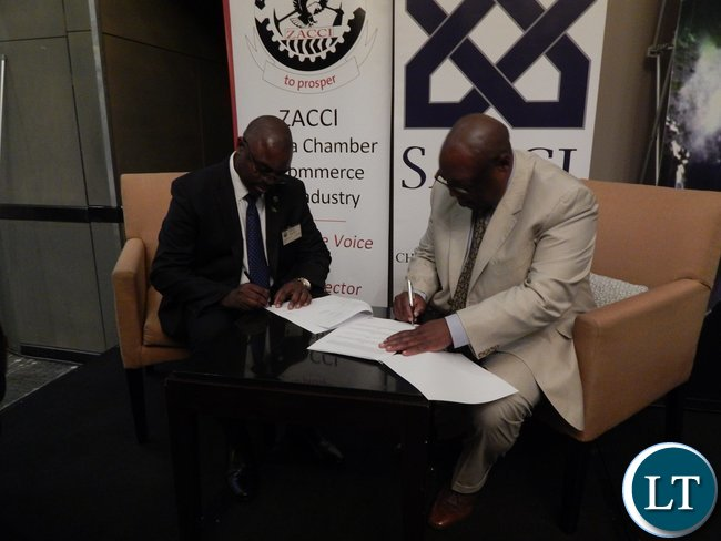 Zambia Association of Chambers of Commerce and Industry vice-president Dr. Chi..Kawesha and South Africa Chamber of Commerce and Industry representative, Mr. Vuyo Khumalo sign a memorandum of understanding at the launch of the Zambia-South Africa Business Council in Johannesburg