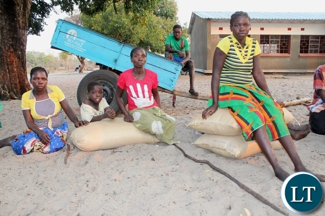 Nasilele Lyamba (r) and her sister Justina Lyamba (l) both victims of Spastic Paralysis (Konzo) disease receive relief maize bags at Lwatembo Primary School from the government in Mongu