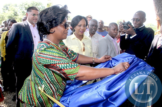 First Lady Esther Lungu and Steven Din, KCM Chief Executive Officer cuts a ribbon during the commissioning of Hellen Bridge Constructed by KCM in Shimulala area in Chingola on Tuesday, December 8,2015. The First Lady was in Chingola where she checked and witnessed various projects that are being undertaken by various stakeholders and those that are undertaken by Konkola Copper Mine (KCM) under Corporate Social responsibility -Picture by THOMAS NSAMA