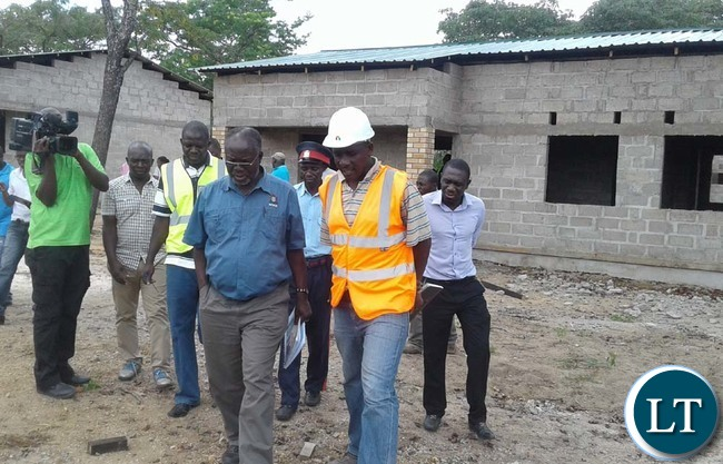 WORKS and Supply deputy Minister Mutaba Mwali (in blue shirt) with Anita Construction Limited site foreman Christopher Nkausu (in a helmet) inspecting 20 low-cost housing units for civil servants in Mulobezi district. Picture y CHILA NAMAIKO