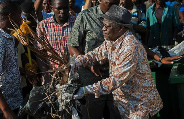 Tanzanian President John Magufuli joins a clean-up event outside the State House in Dar es Salaam on December 9, 2015 Magufuli cancelled Independence Day celebrations and ordered a national day of clean-up instead. (AFP Photo/Daniel Hayduk)