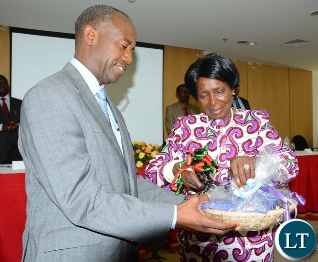 Vice President Inonge Wina cuts the ribbon whilst DMMU Coordinator Patrick Kangwa helps in holding the basket during the Launch of the Disaster Management Policy and Settlement at Government Complex