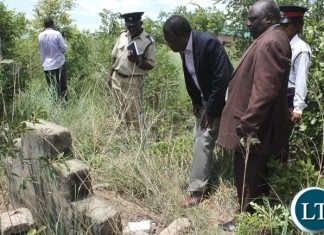 Mongu District Commissioner Susiku Kamona (c) and his Town Clerk Mwiya Mwiya (l) checking the dates on the tomb stone on a grave site yesterday which encroachers who are building houses in the old Mongu Cemetery are demolishing.