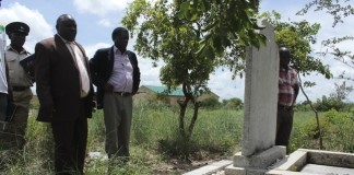 Mongu District Commissioner Susiku Kamona (c) and his Town Clerk Mwiya Mwiya (r) checking the dates on the tomb stone on a grave site yesterday which encroachers who are building houses in the old Mongu Cemetery are demolishing.