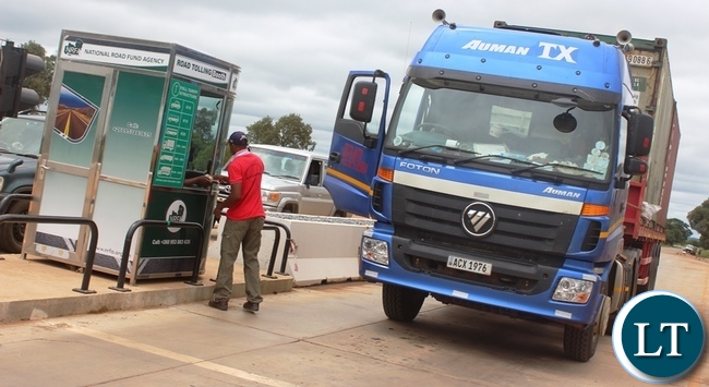 Tollgates have been commissioned at both Manyumbi and Kafulafuta. In the Picture , a Rosa Bus driver paying a toll fee in accordance with the law at Manyumbi Tollgates in Kapiri Mposhi District