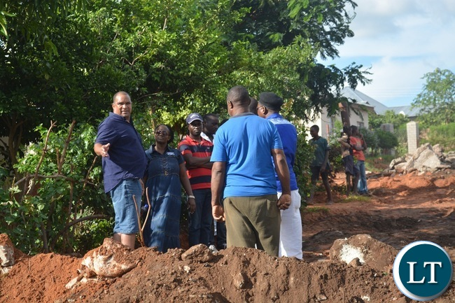 Livingstone Member of Parliament Lawrence Evans (far left) gestures as Livingstone Town Clerk Vivian Chikoti (next to him) looks on as he was inspecting some roads and houses damaged by the recent heavy rains in the tourist capital.