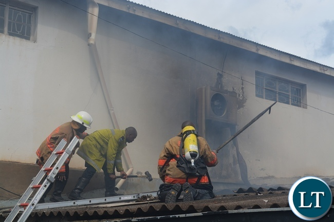 Some fire fighters trying to stop the fire that destroyed Bata town centre outlet Livingstone