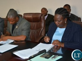 Permanent Secretary of the Ministry of Youth Sport and Child Development Ms Agnes M Musunga sings the memorandum of implementation of the empowerment scheme for the youth bus drivers with Secretary General of the Public and private bus drivers Associations of Zambia Mr Majuru