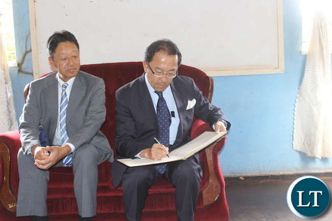 Japanese Ambassador to Zambia Mr. Kiyoshi Koinuma(Right) signing in the visitors' book during a courtesy call at Monze District Commissioner Mr. Cyprian Hamanyanga's office