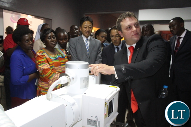 Fuji Film South Africa Engineer Mr. Anton Meyer(left) demonstrates how the Digital X-Ray Machine donated by Japanese government works as Japanese Ambassador Mr. Kiyoshi Koinuma (centre in spectacles), Fuji Film President M. Ryosuke Miki,(left in grey suit), Japanese Embassy staff, and Zambian health officials watch.
