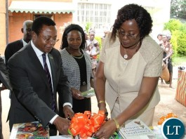 Minister of Community Development and Social Welfare,Emerine Kabanshi and her Permanent Secretary,Davy Chikamata cut the ribbon during the handover of books to Kitwe Community and development Social Welfare College by Books for Africa in Lusaka