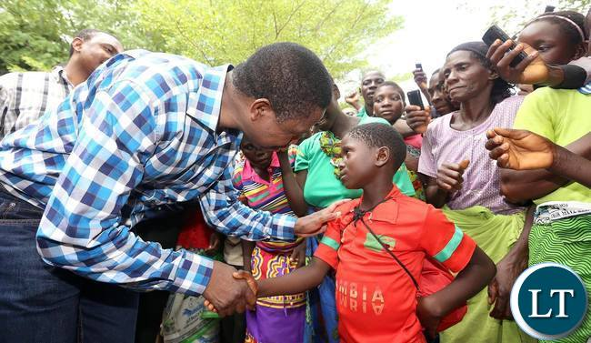 President Lungu talking to one of the local children who came to get a glimpse of him