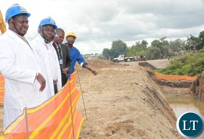 Minister of Local  Government and House,Stephen Kampyongo (c),His Worship the Mayor of the Greater City of Lusaka,George Nyendwa checks the  drainage (l)during the ground breaking in Garden Compound
